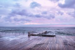 Very early morning at sea. A wooden desert pier. Black Sea. Soft soft tones and focus. A gentle sea Royalty Free Stock Images