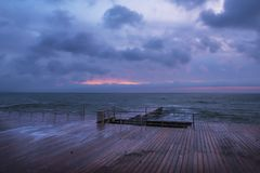 Very early morning at sea. A wooden desert pier and the dawn that is beginning to form. Black Sea Stock Images