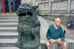 Free Very Elderly European Man With Nordic Walking Sticks And Mythical Chinese Imperial Lion Guard. Royalty Free Stock Photography - 164955387