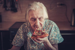Very elderly woman eating a piece of pizza at home. Royalty Free Stock Images