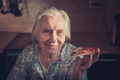 Very elderly woman eating a piece of pizza at home. Stock Image
