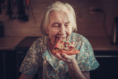 Very elderly woman eating a piece of pizza at home. Stock Photo