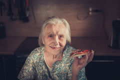 Very elderly woman eating a piece of pizza at home. Stock Photography