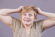 Very emotional angry woman with gold teeth on a gray background. Stock Photo