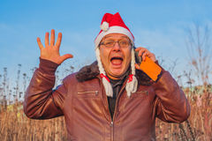 Very emotional man in funny santa hat talking on the phone Royalty Free Stock Photography