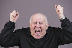 Very emotional man screams on a gray background Royalty Free Stock Image
