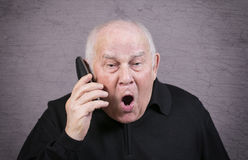 Very emotional man with the telephone handset screams on a gray background Royalty Free Stock Photos