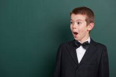Very emotional school boy portrait near green blank chalkboard background, dressed in classic black suit, one pupil, education con Stock Photos