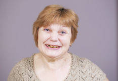 Very emotional woman with gold teeth smiling  on a gray background. Stock Images