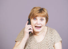 Very emotional woman with gold teeth with the telephone handset on a gray background. Royalty Free Stock Photography