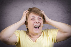 Very emotional woman screams in grief on a gray background Stock Image
