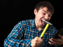 A very evil man breaks a phone or tablet with a hammer. Powerful emotions. royalty free stock images