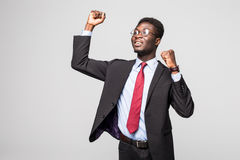 Very excited African business man with raised hands in the air isolated grey background Stock Photo