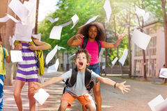 Very excited boy scream with friends throws paper royalty free stock photography