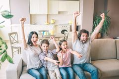 Very excited and happy family are cheering. They hold their hands up. People scream and yell. They rejoy. Very excited and happy family are cheering. They hold stock images