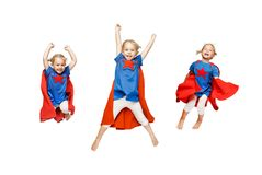 Very excited little girl dressed like hero jumping isolated on white background. Stock Photo