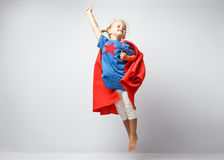 Very excited little girl dressed like superhero jumping alongside the white wall. Stock Images