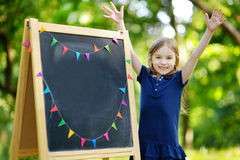 Very excited little schoolgirl by a chalkboard. Adorable little schoolgirl feeling extremely excited about going back to school Royalty Free Stock Photo