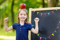 Very excited little schoolgirl by a chalkboard Stock Image