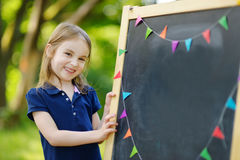 Very excited little schoolgirl by a chalkboard. Adorable little schoolgirl feeling extremely excited about going back to school Royalty Free Stock Photos
