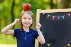 Very excited little schoolgirl by a chalkboard. Adorable little schoolgirl feeling extremely excited about going back to school Stock Photos