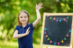 Very excited little schoolgirl by a chalkboard Royalty Free Stock Photography