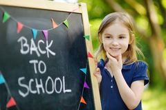 Very excited little schoolgirl by a chalkboard. Adorable little schoolgirl feeling extremely excited about going back to school Stock Photo