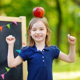 Very excited little schoolgirl by a chalkboard. Adorable little schoolgirl feeling extremely excited about going back to school Stock Image