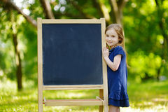 Very excited little schoolgirl by a chalkboard. Adorable little schoolgirl feeling very excited about going back to school Stock Images