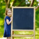 Very excited little schoolgirl by a chalkboard Royalty Free Stock Image