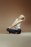 Very Expressive blonde girl in a white torn top and jeans sit on Stock Photos