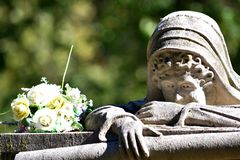 Weeping lady receives a bouquet. A very famous grave marker with many ghost stories about it. The weeping lady still receives flowers from time to time even royalty free stock photos