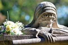 Weeping lady receives a bouquet. A very famous grave marker with many ghost stories about it. The weeping lady still receives flowers from time to time even stock photos