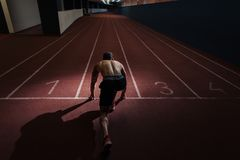 Very fit man on a an indoor track preparing to run. In the start position royalty free stock image