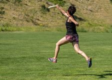 Flying disc running and catch midair. A very fit woman in her late 40's, running at full speed while exercising, leaps into the air and catches a flying royalty free stock photos