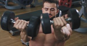 A very fit young man is at the gym working out and in his triceps, he is doing this by lifting a heavy weight at the gym. 4k stock video footage