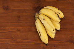 Very fresh yellow banana bunch on brown wooden table Royalty Free Stock Photography