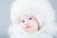 Very funny baby in a white snow suit and big fur hat Royalty Free Stock Images