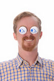 Very funny young man with toys. On his eyes Royalty Free Stock Images