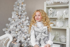 Very glad little girl holds a gift box at hands and looks up in Christmas Stock Images