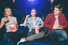 Very good young friends are sitting together in cinema. Blonde gir and boy are looking at each other and smiling. She is. Holding phone in hands. Brunette is Stock Image