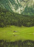 A very green mountain valley and small alpine hut reflected in Eibsee, Germany stock image