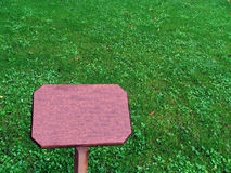 Very green nice lawn of herbs with wooden pointer Stock Photography