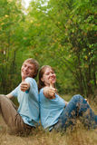 We are very happy!. Young happy loving couple with thumbs up in summer nature Royalty Free Stock Photography