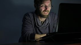 Very happy bearded man working on laptop and begins to very surprised and upset.  stock video
