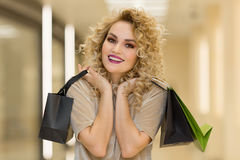 Very happy beautiful young woman in casual clothing with shopping bags, at centre or mall. Model in sales, shop, retail, consumer concept Stock Images