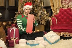 A very happy Christmas to you. Happy man with Christmas gift boxes. Guy is celebrating Christmas at home. Man in santa royalty free stock image