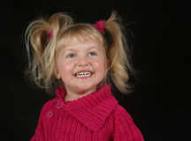 Very Happy Girl. A cute preschool girl smiling in a pink sweater Royalty Free Stock Images