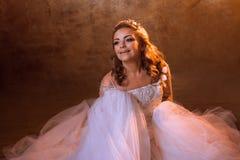 Very happy girl bride in luxurious wedding dress sitting on the floor, portrait in Golden tones. Beautiful girl bride in a luxurious wedding dress, portrait in Royalty Free Stock Images