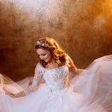 Very happy girl bride in luxurious wedding dress sitting on the floor, portrait in Golden tones. Beautiful girl bride in a luxurious wedding dress, portrait in Stock Photography